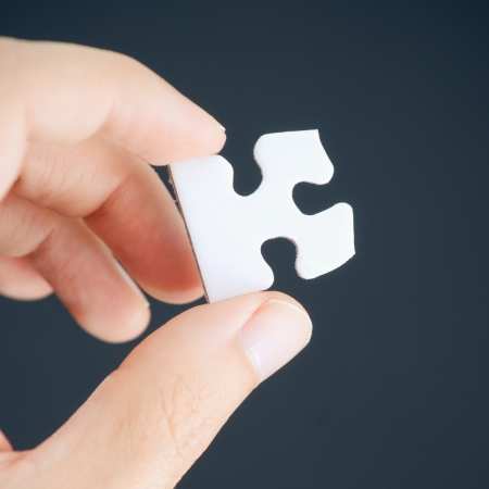 Hand holding single puzzle piece   photo