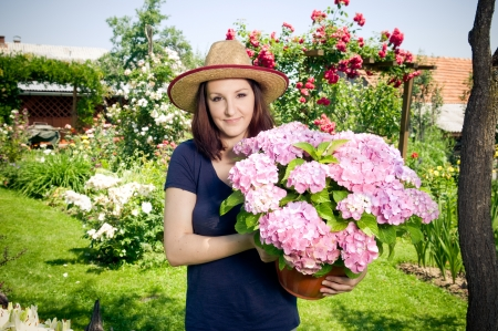 Young woman holding a pot with flowers in her garden Standard-Bild
