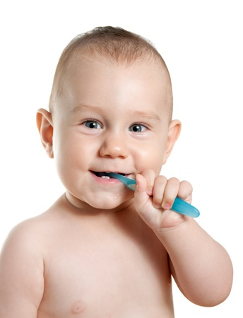 Baby boy cleaning his teeth. White background.  photo