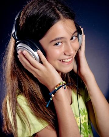 trendy girl: Cute girl with headphones smiling. Dark background.