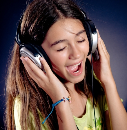 Cute girl with headphones singing.  Dark background. Stock Photo