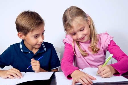 children studying: Schoolchildren siting and writing together. Simple background.  Stock Photo