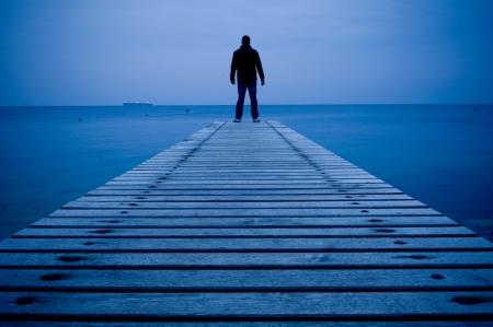 Homme debout sur un ponton en bois au crépuscule