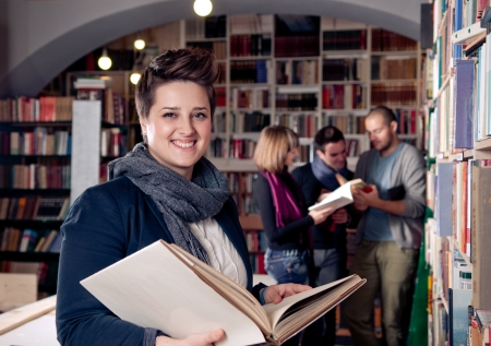 Smiling female student holding book  Students in the background Stock Photo - 16272969