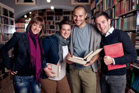 Groep studenten in een bibliotheek glimlachend en het bedrijf boeken