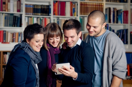 Touch screen tablet computer - group of students in library Stock Photo - 16304653