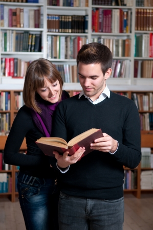 Couple of students at the library reading a book Stock Photo - 16304656