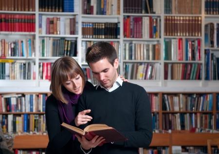 Couple d'étudiants à la bibliothèque de lire un livre Banque d'images