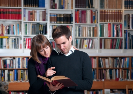 Paar von Studenten in der Bibliothek ein Buch zu lesen