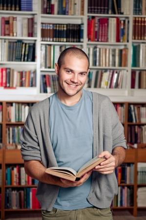 Mannelijke student staan in de bibliotheek, houdt boek