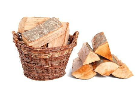 Brandhout in houten mand op wit wordt geïsoleerd Stockfoto