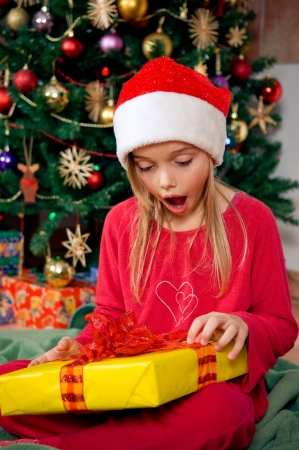little girl surprised: Surprised little girl holding her gift in front of christmas tree Stock Photo