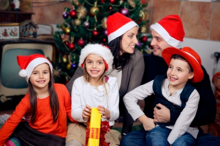 Happy family sitting in front of christmas tree  Celebrating Christmas   photo