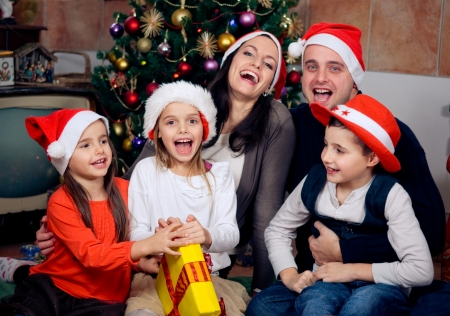 Happy family sitting in front of christmas tree. Celebrating Christmas.  photo