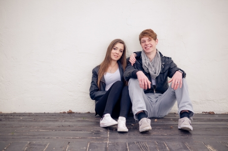 Teenage couple sitting by the wall  photo
