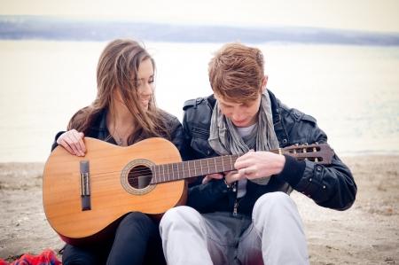 Jong meisje met akoestische gitaar en haar vriendje op de bach Stockfoto