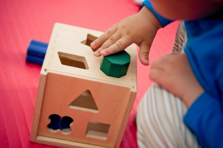 sorting: Toddler playing with wooden shape sorter  Stock Photo