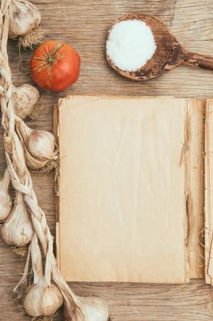 Oude lege kookboek, knoflook, tomaat en zout