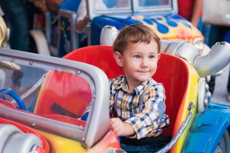 Kleine jongen rijdt een auto in pretpark