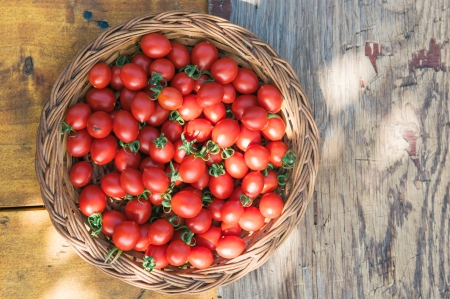 Cherry tomatos in basket on wooden table photo