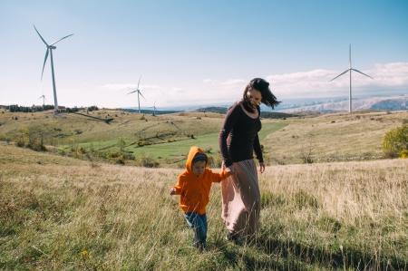 Moeder en zoon in de natuur. Windturbines op de achtergrond.