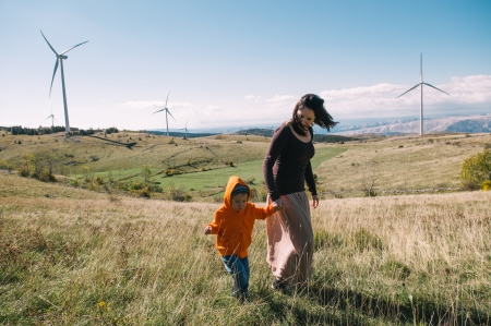 Mother and son in nature. Wind turbines in the background. photo