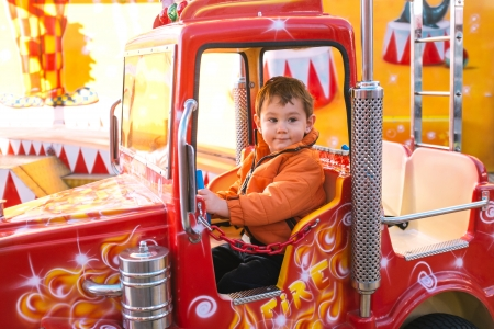 Little boy riding a small fire truck in amusement park photo