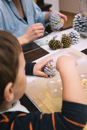 Weinig jongen en zijn moeder schilderen dennenappels voor Kerstmis Stockfoto