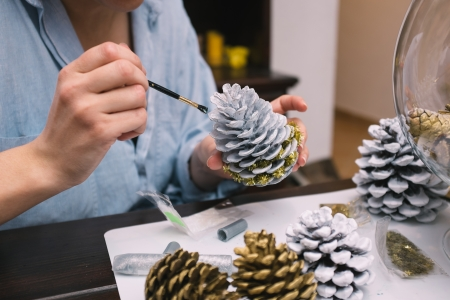 decoration work: Woman painting pine cones at her home