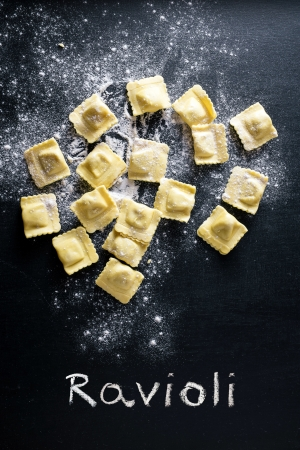 Ravioli pasta and flour on black background