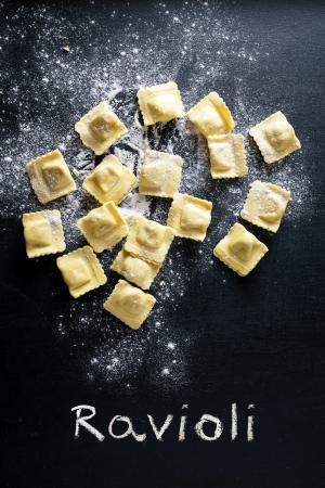 Ravioli pasta en bloem op zwarte achtergrond