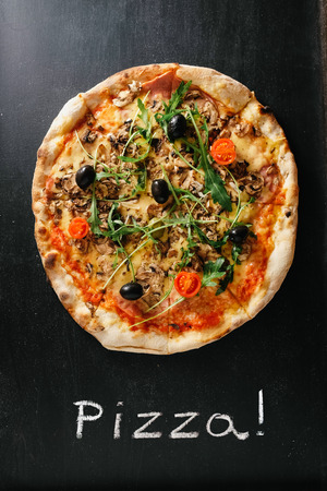 Delicious pizza on black surface  photo