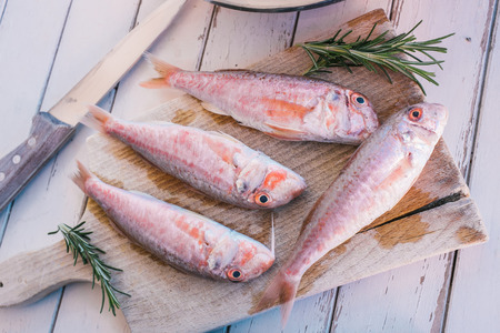Mullet fish and rosemary on wooden table