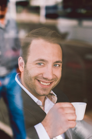 half dressed: Handsome smiling man drinking espresso in cafe looking through the window