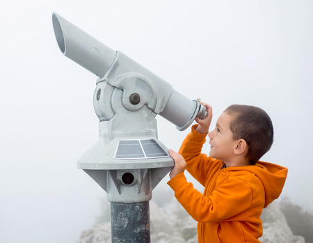 enlargement: Boy looking into the sky through a monocular Stock Photo