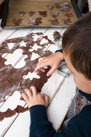 Little boy making gingerbread men photo