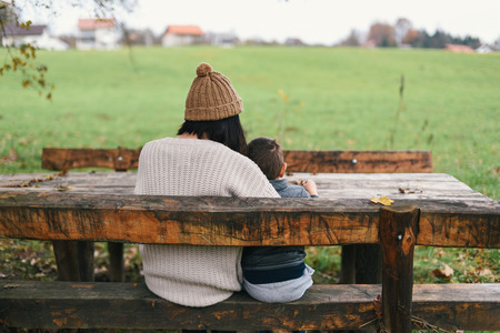 mother on bench: Mother and her son sitting on the wooden bench in countryside Stock Photo