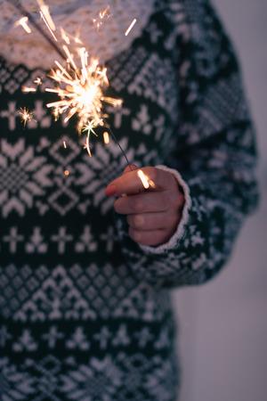 Female hand holding sparkler photo