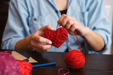 workshop: Woman creating red woolen heart