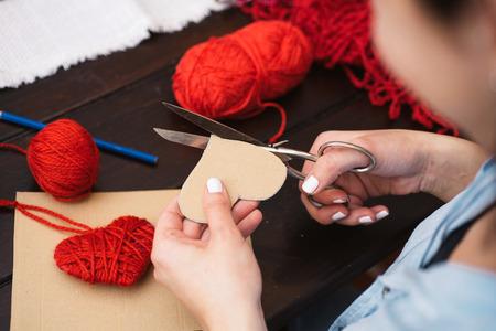 Donna creando cuore rosso di lana