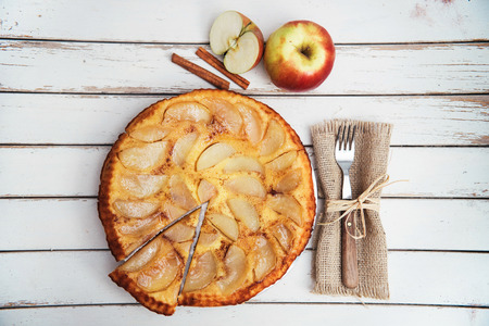Apple cake with cinnamon on rustic white table