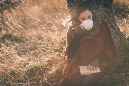 Woman in nature drinking tea or coffee. Writing in a notebook