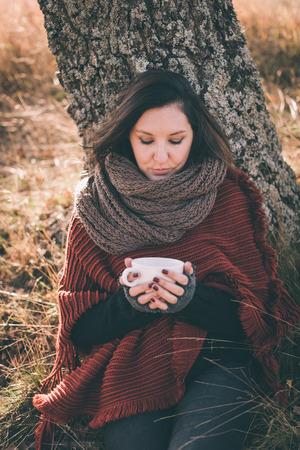 women sitting: Woman in nature holding cup with tea or coffee Stock Photo