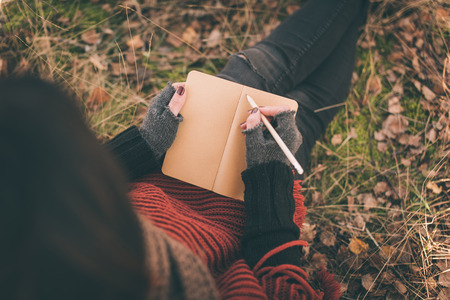 Woman in nature writing in a notebook 스톡 콘텐츠
