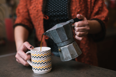 with coffee maker: Woman pouring coffee from vintage coffee maker