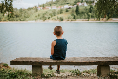 Introverted boy sitting on the bench by the lake Stock Photo