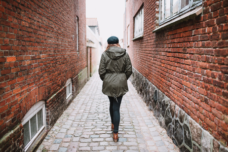 Lonely female person walking in the street, photographed from behind  Stock Photo