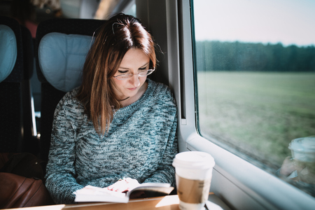 Women reading book on the train Imagens - 75957695