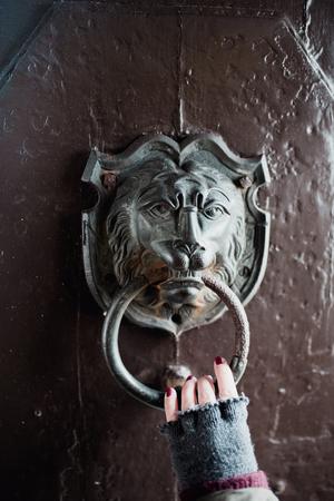 door knob: Hand holding metal lion door knocker on a wooden door