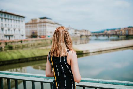 Vrouw staat op een brug in Florence